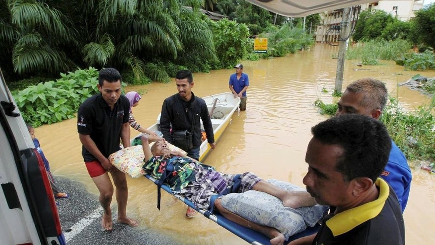 In this Wednesday, Dec. 24, 2014 photo, members of Malaysia Civil Defense Department evacuate a disabled elderly man from a flooded village in Tumpat, Kelantan state, Malaysia. Malaysian Prime Minister Najib Razak said Friday, Dec. 26 he was cutting short his U.S. vacation to deal with the worst floods in the country in decades that have killed five people and displaced more than 100,000. (AP Photo) MALAYSIA OUT, NO SALES, NO ARCHIVE