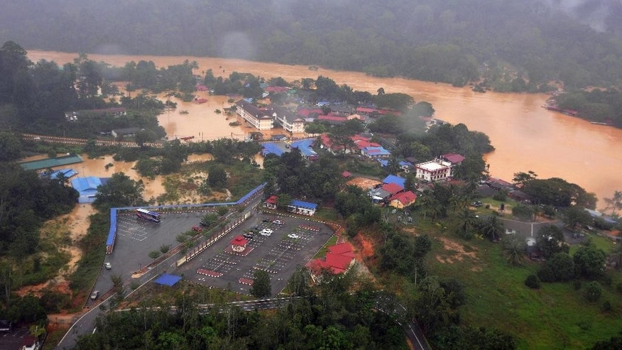 In this Wednesday, Dec. 24, 2014 photo, numbers of houses and buildings along a flooded river stand in muddy water in Malaysia National Park in Kuala Tahan, Pahang state, Malaysia. Malaysian Prime Minister Najib Razak said Friday, Dec. 26 he was cutting short his U.S. vacation to deal with the worst floods in the country in decades that have killed five people and displaced more than 100,000. (AP Photo) MALAYSIA OUT, NO SALES, NO ARCHIVE