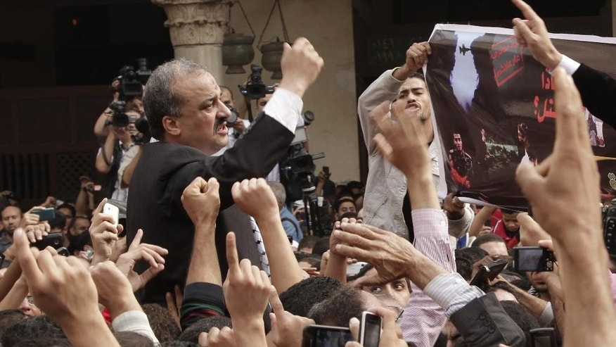 FILE - In this Friday, Nov. 16, 2012 file photo, protesters led by senior Muslim Brotherhood figure Mohammed el-Beltagy, center left, and former member of the Egyptian Parliament, Essam Soltan, unseen, chant slogans against the Israeli invasion of Gaza, in Al-Azhar mosque after Friday prayers in Cairo, Egypt. On Saturday, Dec. 27, 2014, el-Beltagy, a leading Brotherhood member, was sentenced to six years in prison for insulting a panel of judges. Presiding judge Shaaban el-Shami accused el-Beltagy of insulting him during the proceedings for a case in which he and 130 other defendants are accused of staging prison breaks during the January 2011 uprising that toppled longtime leader Hosni Mubarak. (AP Photo/Thomas Hartwell, File)