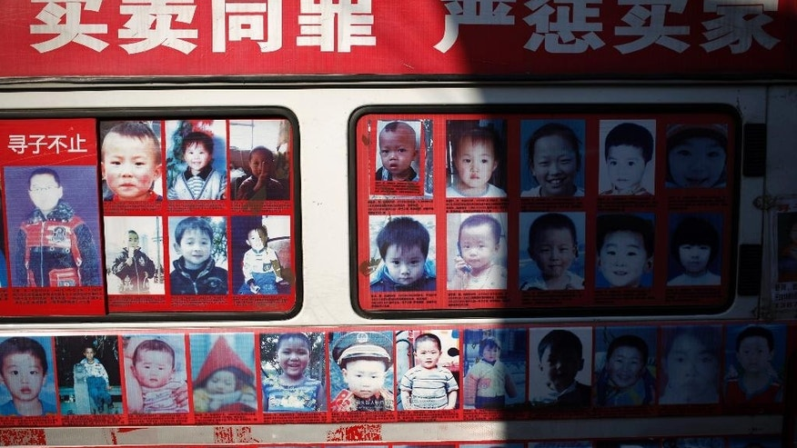 In this Dec. 2, 2014 photo, a van displaying photos of the missing children across China, which created by Xiao Chaohua, to seek public attention to locate the children, is parked outside his house in Beijing, China. As many as 70,000 children are estimated to be kidnapped every year in China for illegal adoption, forced labor or sex trafficking, making it one of the world's biggest markets for abducted children, according to the state-run newspaper China Daily. (AP Photo/Andy Wong)