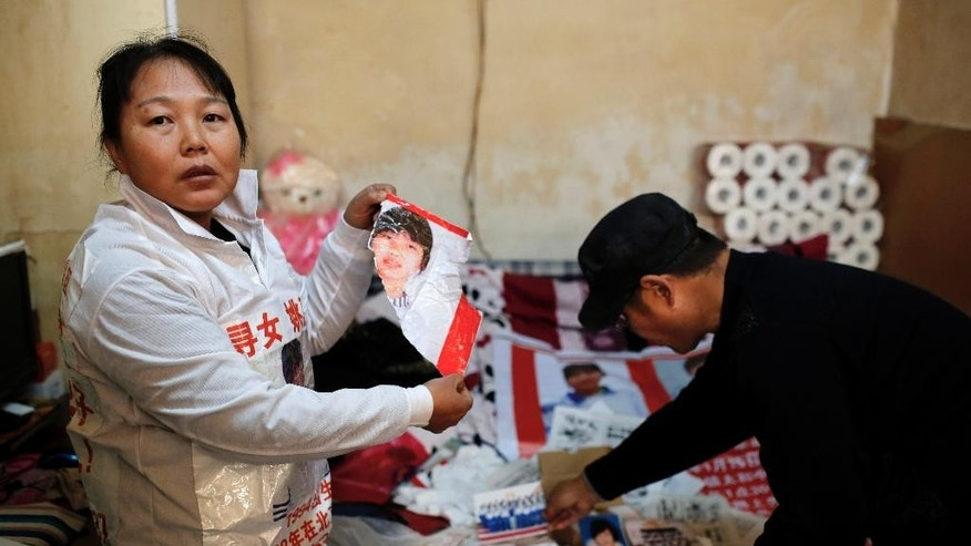 In this Dec. 2, 2014 photo, Zhang Xiuhong, left, shows a ripped poster of her missing daughter, which she says was damaged by police, as her husband Yao Fuji arranges other photos, at their rented room in Beijing, China. Zhang and her husband have since searched all over China for Yao Li, hoping to rescue her from a child trafficking industry that swallows up thousands of boys and girls every year. Along the way, the couple have also been harassed, arrested and jailed repeatedly by police who accuse them of stirring up trouble by taking their search to the streets. (AP Photo/Andy Wong)