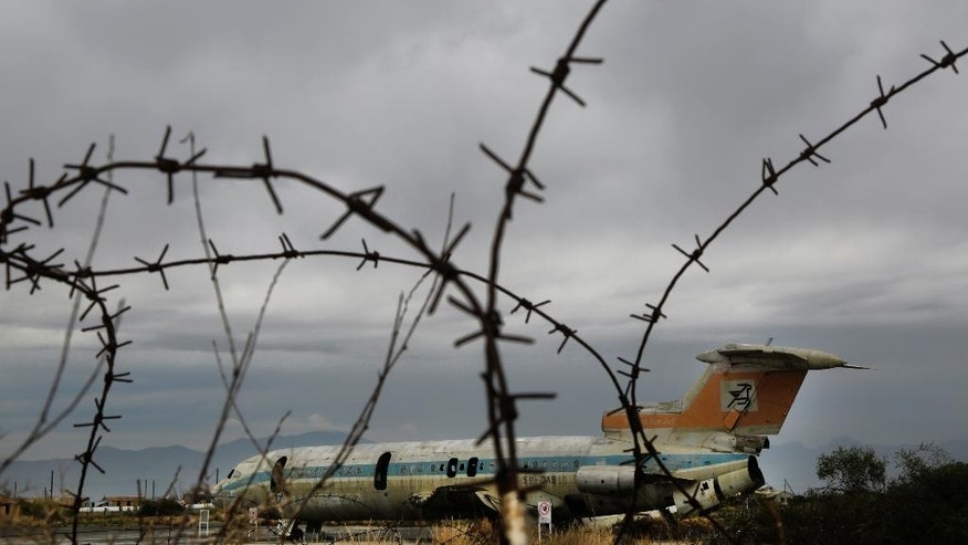 In this Tuesday, Nov. 25, 2014 photo, the rusting hulk of an abandoned Cyprus Airways Trident passenger jet lies behind barbed wire on the tarmac of of the disused Nicosia airport that lies inside a United Nations-controlled buffer zone separating the breakaway Turkish speaking north of ethnically divided Cyprus from the internationally recognized Greek speaking south. Once an emblem of the young republic's growing confidence just 14 years after independence from British colonial rule, the airport overnight became a symbol of a future hijacked by unresolved conflict. (AP Photo/Petros Karadjias)