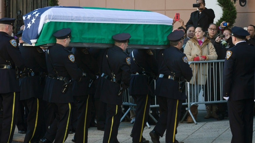 The casket of New York Police Department officer Rafael Ramos arrives to his wake at Christ Tabernacle Church in the Glendale section of Queens, where he was a member, Friday, Dec. 26, 2014, in New York. Ramos was killed Dec. 20 along with his partner, Officer Wenjian Liu, as they sat in their patrol car on a Brooklyn street. The shooter, Ismaaiyl Brinsley, later killed himself. (AP Photo/John Minchillo)