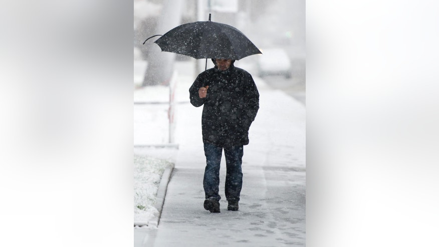 A man makes his way through the snow in Stuttgart, southern Germany, Saturday Dec. 27, 2014. Weather forecasts predict colder temperatures and snowfall in Germany. (AP Photo/dpa, Daniel Naupold)