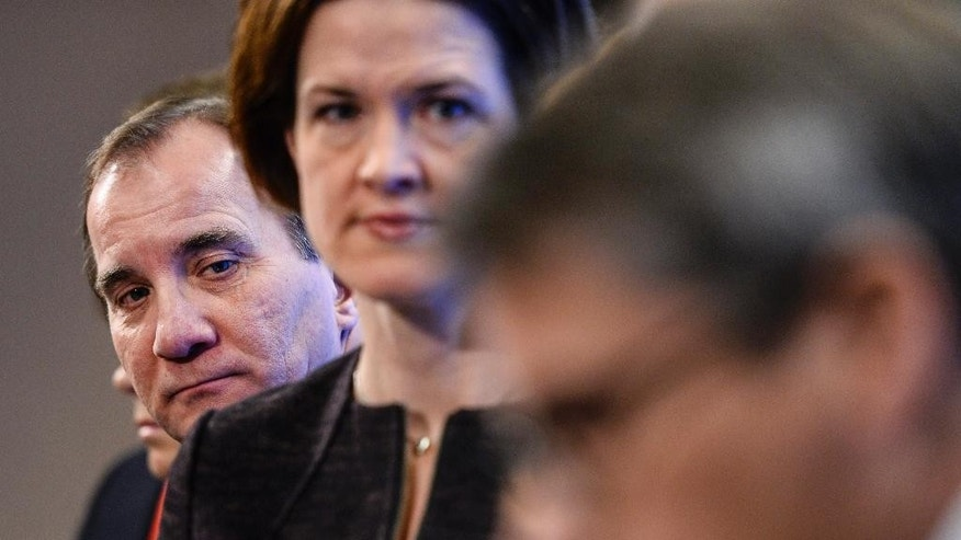 Sweden's Prime Minister and Social Democratic Party  leader Stefan Löfven, left, looks over the shoulder of Moderate Party leader-elect Anna Kinberg Batra speak during a press conference at the Swedish Parliament in Stockholm, Sweden, Saturday, Dec. 27, 2014. During the presser the parties announced that a 'December agreement' on how to rule with a minority government in the parliament, has canceled the plans to run a snap election in March 2015.  (AP Photo / Maja Suslin / TT)  SWEDEN OUT