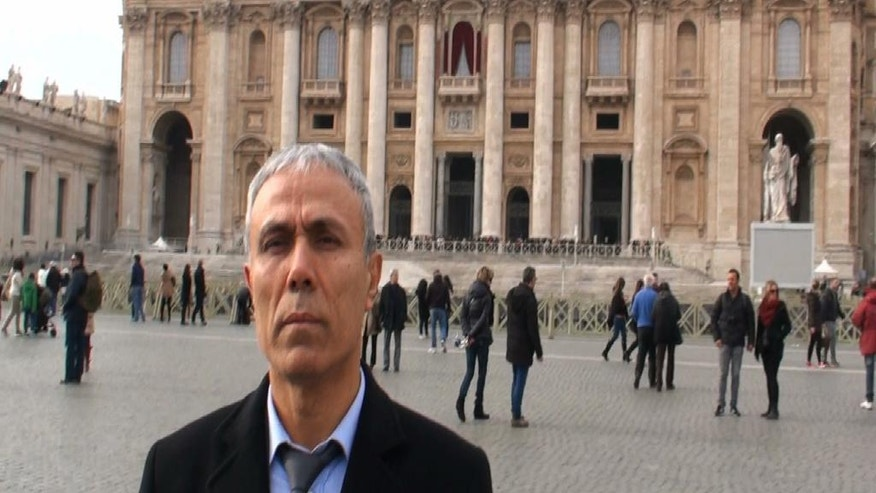 In this image taken from a video provided by Adnkronos International, Ali Agca stands in front of St. Peter's Basilica at the Vatican, Saturday, Dec. 27, 2014. The Turkish gunman who shot and wounded John Paul II in 1981 laid white flowers Saturday on the saint's tomb in St. Peter's Basilica, Vatican officials said. A Vatican spokesman, the Rev. Ciro Benedettini, said the surprise visit by Mehmet Ali Agca, believed to be his first time in the Vatican since the assassination attempt, lasted a few minutes. As with other flowers left by visitors to the tomb, the blossoms were later removed by basilica workers. (AP Photo/Adnkronos International, ho)