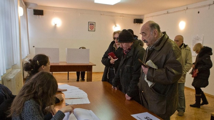 Voters register at a polling station in Zagreb, Croatia, Sunday, Dec. 28, 2014. Croatia's economic woes hung over presidential elections Sunday in which a liberal incumbent faced pressure from a conservative challenger. The vote is seen as a test for the center-left government which has come under criticism for its failure to revive the economy more than one year after Croatia joined the EU. Croatia has one of the weakest economies in the bloc, with unemployment at nearly 20 percent and a six-year recession. Nearly 3.8 million voters can pick from four candidates for the largely ceremonial but influential post. (AP Photo/Darko Bandic)