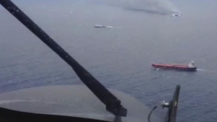 In this image taken from a video released by the Italian Air Force, smoke billows from the Italian-flagged Norman Atlantic, top right, after it caught fire in the Adriatic Sea, Sunday, Dec. 28, 2014. A ferry carrying about 470 people caught fire off the Greek island of Corfu early Sunday, trapping passengers on the top decks as gale-force winds and choppy seas hampered the evacuation. Greek and Italian rescue helicopters and vessels struggled to reach the stricken ferry, battered by 90 kilometer per hour (55 mph) winds that sent it up toward the strait between Italy and Albania. (AP Photo/Italian Air Force)