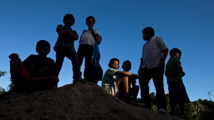In this Sunday, Nov. 23, 2014 photo, 11-year-old Maynor Ayala, center, sits on a dirt mound, with his friends in the Progreso neighborhood of Tegucigalpa, Honduras. Maynor's father wants him to make the illegal trip north to join him in the United States. But for now, Maynor choses to stay with his mother and play soccer with his friends. (AP Photo/Esteban Felix)