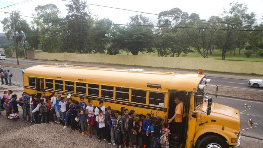 In this Sunday, Nov. 22, 2014 photo, children of the project that coach Luis Lopez created a year ago, line up to board a bus for the first football game outside their neighborhood at El Progreso in Tegucigalpa, Honduras. When the small California-based Kahl foundation learned about Lopez's program using soccer to show children a way out of the violence, it sent money to upgrade the field, buy equipment and rent buses so the children could travel around Tegucigalpa to play other teams. (AP Photo/Esteban Felix)