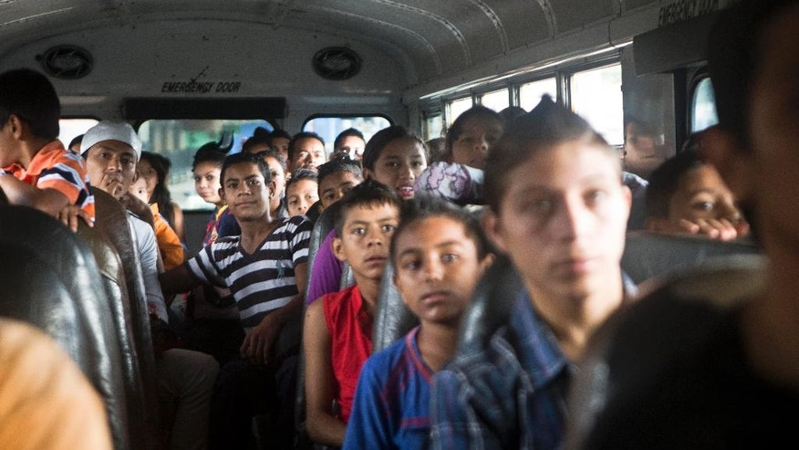 "In this Sunday, Nov. 22, 2014 photo, children watch a music video while riding on a bus, of a popular reggaeton song, called ""Cute Girls."" ""Most cute girls would die to have a bad boy,"" the song says, talking about pulling the girl's hair and denigrating her. ""I know you like those things ... I have to shoot, insult you, lose my senses, hit you to be able to love you."" The children's soccer coach Luis Lopez was traveling in a different car and didn't see the video. But when he heard about it, he turned furious at practice. Lopez believed that if they were enjoying a video that depicts violence, discrimination, and fast, illegal money, his efforts had been in vain. (AP Photo/Esteban Felix)"