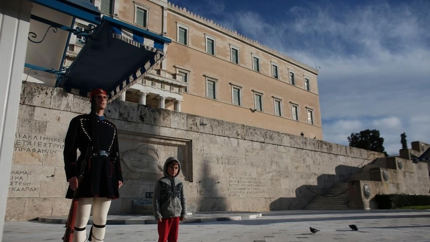 A child poses for photos next to a Greek Presidential Guard,  at the monument of the unknown soldier in front of the parliament building in Athens on Saturday, Dec. 27 2014. A crucial vote in Parliament Monday will determine whether Greece will have a new President of the Republic or will have to go to early elections in about a month for another Parliament to elect one. (AP Photo/Kostas Tsironis)