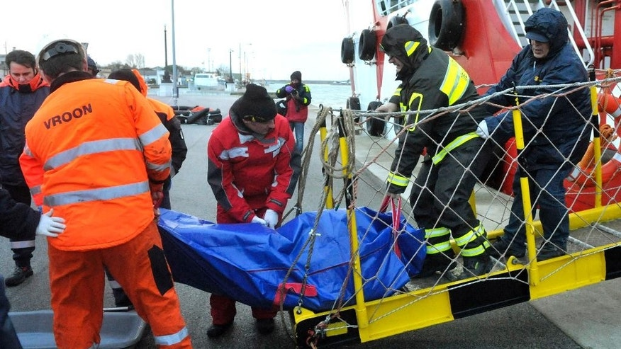 Firefighters carry the body of one of the victims after the 86-meter-long (290-foot) Turkish ship Gokbel went down after colliding with the 97-meter-long (320-foot) Belize-flagged Lady Aziza, at the Marina di Ravenna harbor, Italy, Sunday, Dec. 28, 2014. A Turkish cargo ship collided with another merchant vessel and sank near a foggy Italian port in the northern Adriatic on Sunday, killing a crew member and leaving five crew missing in cold, rough seas, officials said. Coast Guard Cmdr. Franco Maltese said six crew members were initially rescued and brought to the port of Marina di Ravenna; one of those rescued later died in the hospital. He said searchers spotted what was believed to be a corpse in the choppy waters. (AP Photo/Marco Vasini)