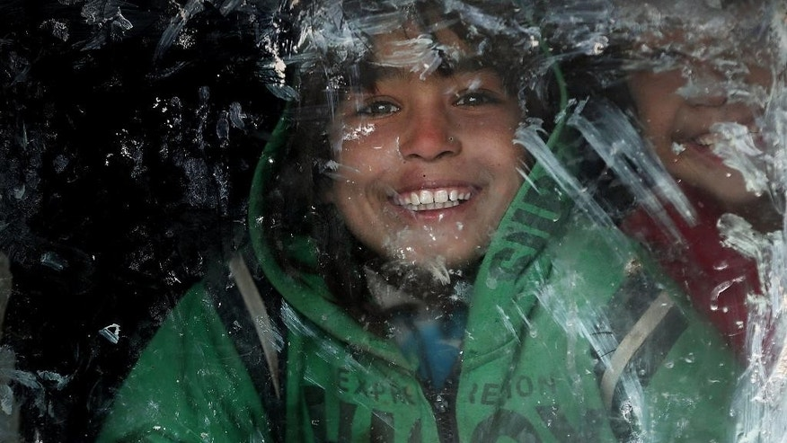In this Wednesday, Dec. 24, 2014 photo, an internally displaced Afghan girl smiles as she looks outside a window at a camp in Kabul, Afghanistan. (AP Photo/Massoud Hossaini)