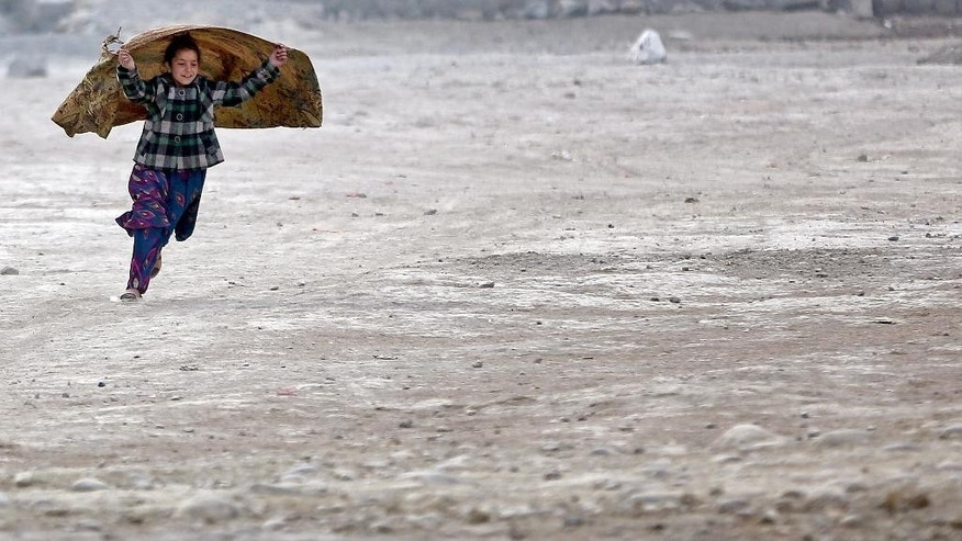 In this Wednesday, Dec. 24, 2014 photo, an internally displaced Afghan girl runs at a camp in Kabul, Afghanistan. (AP Photo/Massoud Hossaini)