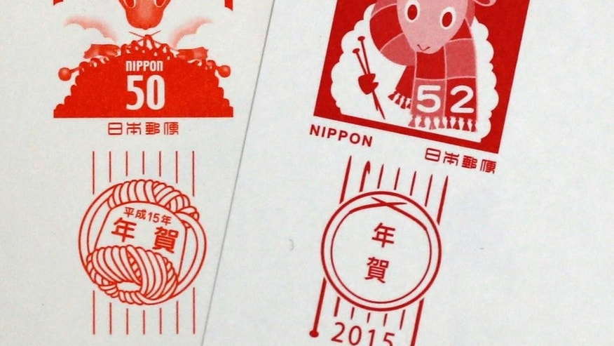 In this Dec. 30, 2014 photo, sheep designs on postage stamps are seen on New Year's greeting cards, 2003 issue, left, and 2015 issue, right. When millions of Japanese get their customary New Year's greeting cards Monday, the sheep that's on the postage stamps will have finished knitting the scarf it began 12 years ago.  In 2003, the stamp on the cards issued by the post office had as its design a fluffy sheep busily knitting a scarf. This year, it's wearing the scarf, and holding the knitting needles. (AP Photo/Shuji Kajiyama)