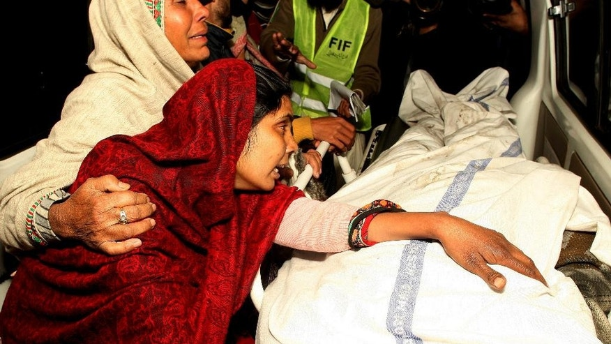 A Pakistani woman mourns over the dead body of a family member after a fire broke out in a building, in Lahore, Pakistan, Monday, Dec. 29, 2014. A fire broke out in shopping center killing many people, police said. (AP Photo/K.M. Chaudary)