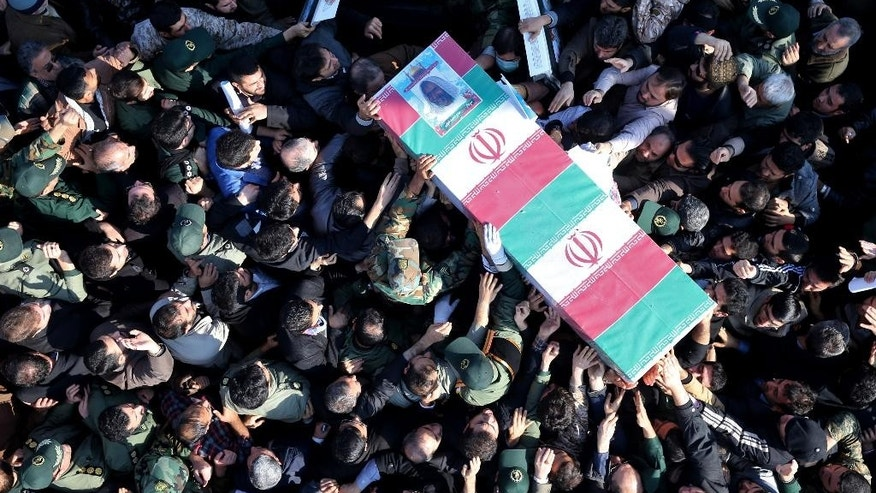 "Iranian civilians and armed forces members carry the flag draped coffin of Brig. Gen. Hamid Taqavi, a senior Revolutionary Guard commander who was killed during a battle against the Islamic State extremist group in Iraq, in his funeral ceremony outside the Guard compound in Tehran, Iran, Monday, Dec. 29, 2014. The Guard said Sunday that Taqavi was ""martyred while performing his advisory mission"" in Samarra, a town north of Baghdad that is home to a major Shiite shrine. He is the highest ranking Iranian officer known to have been killed abroad since the Iran-Iraq war in the 1980s, in which he fought. (AP Photo/Ebrahim Noroozi)"