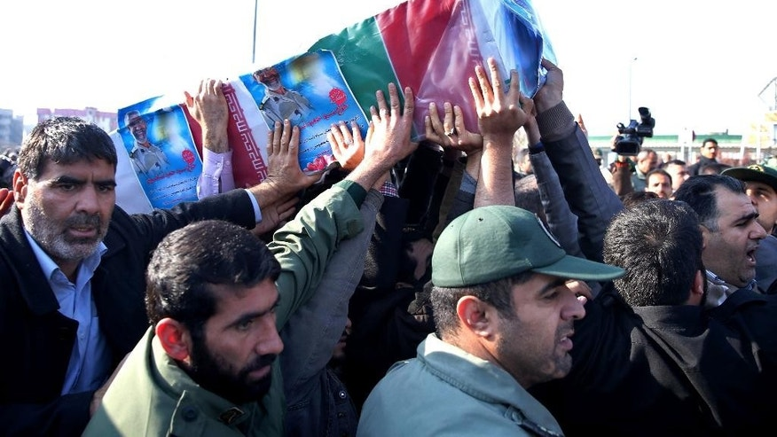 "A group of people and Iranian Revolutionary Guard members carry the flag draped coffin of Brig. Gen. Hamid Taqavi, a senior Revolutionary Guard commander who was killed during a battle against the Islamic State extremist group in Iraq, in his funeral ceremony outside the Guard compound in Tehran, Iran, Monday, Dec. 29, 2014. The Guard said Sunday that Taqavi was ""martyred while performing his advisory mission"" in Samarra, a town north of Baghdad that is home to a major Shiite shrine. He is the highest ranking Iranian officer known to have been killed abroad since the Iran-Iraq war in the 1980s, in which he fought. (AP Photo/Ebrahim Noroozi)"