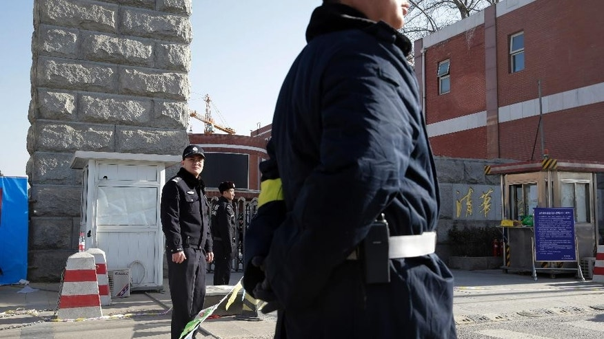 Chinese policemen stand guard near the closed main entrance gate of Tsinghua high school in Beijing, China Monday, Dec. 29, 2014. A scaffolding collapse at the high school Monday morning killed and injured people, Chinese state media reported. A high school official with the surname Jiang told The Associated Press that all the victims were workers building a school gymnasium. He said no teachers or students were involved. (AP Photo/Andy Wong)