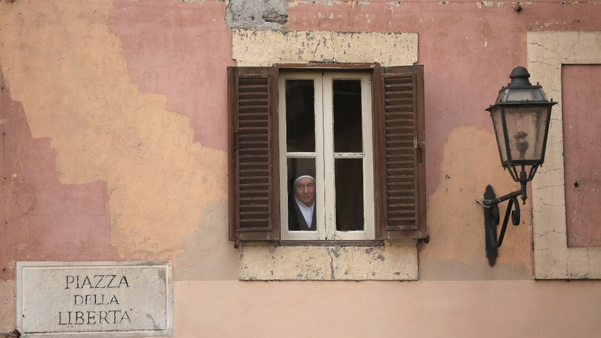 ROME, ITALY - FEBRUARY 28:  A nun looks through a window as she waits for Pope Benedict XVI to address pilgrims, for the last time as head of the Catholic Church, from the window of Castel Gandolfo where he will start his retirement today on February 28, 2013 in Rome, Italy. Pope Benedict XVI has been the leader of the Catholic Church for eight years and is the first Pope to retire since 1415. He will stay at the Papal Summer residence of Castel Gandolfo until renovations are complete at a monastery in the grounds of the Vatican and will be known as Roman Pope Emeritus.  (Photo by Christopher Furlong/Getty Images)