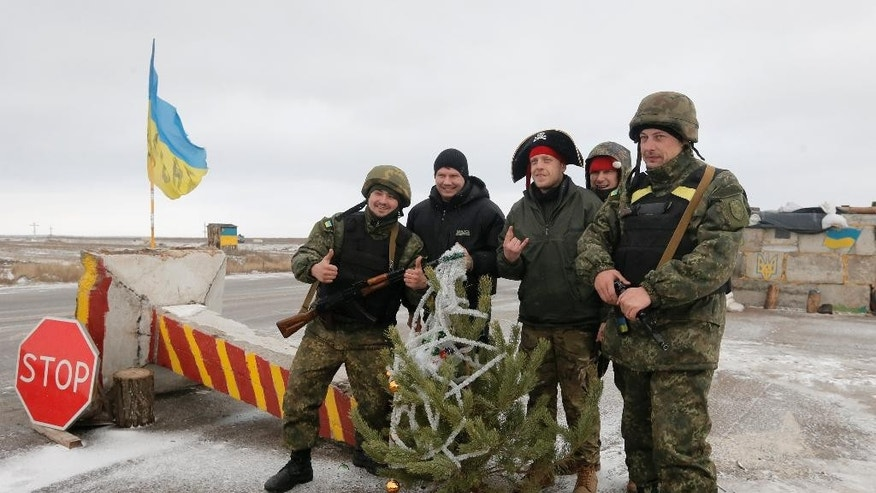 Ukrainian army soldiers pose for photo with volunteers at a check point in Debaltsevo, Donetsk region, Ukraine, Ukraine Sunday, Dec 28, 2014. Volunteer groups across Ukraine are raising funds and buying equipment for soldiers fighting in the east of the country against pro-Russian separatists and often delivering the supplies directly to the soldiers themselves. In Kiev alone, some 30 volunteer groups involve several thousand people. (AP Photo/Efrem Lukatsky)