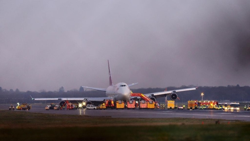 "Emergency services gather around a Virgin Atlantic Boeing passenger jet after it performed an emergency landing at Gatwick Airport following a landing gear fault, London, Monday, Dec. 29, 2014. The airline says the plane undertook ""a non-standard landing procedure"" because of ""a technical issue with one of the landing gears."" (AP Photo/PA, Gareth Fuller) UNITED KINGDOM OUT, NO SALES, NO ARCHIVE"