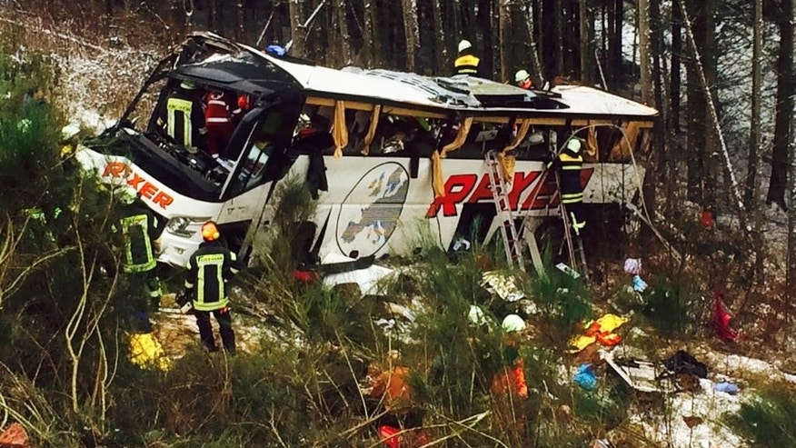 Rescue workers are busy at the site were a bus crashed on a highway near Bad Hersfeld, central Germany, Tuesday, Dec. 30, 2014. Police say the crash occurred after a car collided with the bus, causing it to veer off the road and down a slope. Several people died in the crash and about forty haven been injured. (AP Photo/dpa, osthessen-news/Hans-Hubertus Braune)