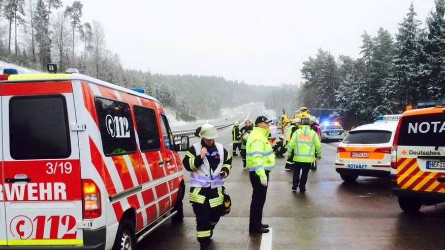 Rescue workers are busy at the site were a bus crashed on a highway near Bad Hersfeld, central Germany, Tuesday, Dec. 30, 2014. Police say the crash occurred after a car collided with the bus, causing it to veer off the road and down a slope. Several people died in the crash and about forty haven been injured. (AP Photo/dpa, Osthessen-News)