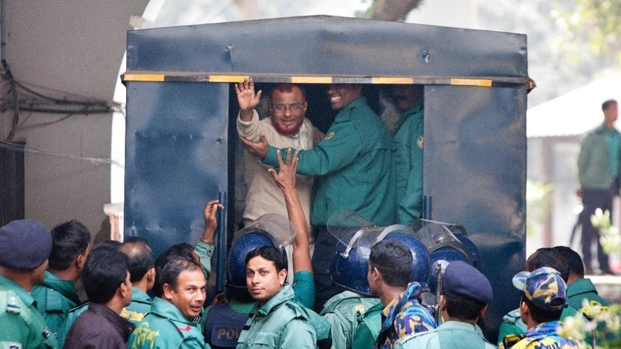 A.T.M. Azharul Islam, assistant secretary general of the Jamaat-e-Islami party, waves his hand as he enters a police van after a special tribunal sentenced him to death in Dhaka, Bangladesh, Tuesday, Dec. 30, 2014. A special tribunal in Bangladesh has sentenced the senior Islamist party leader to death for leading a militia that committed mass killings and rape during the country's 1971 independence war against Pakistan. He is the eighth convicted leader from Jamaat-e-Islami, which openly campaigned against independence and worked as the core political force in favor of West Pakistan, now Pakistan. (AP Photo/ Suvra Kanti Das)