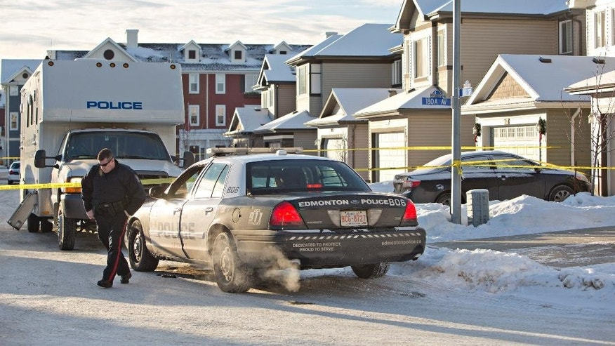 Police investigate the scene where multiple deaths occurred overnight in Edmonton, Alberta, Tuesday, Dec. 30, 2014. (AP Photo/The Canadian Press, Jason Franson)