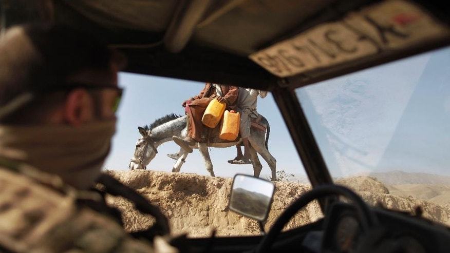 FILE - In this Sept. 12, 2009 file photo a German ISAF soldier passes children on a donkey during a patrol outside Feyzabad, east of Kunduz, Afghanistan. German media are reporting that the country's army contributed to a list of insurgents targeted for killing or detention by NATO in Afghanistan. Opposition lawmakers called Tuesday, Dec. 30, 2014, for an investigation into the reports, saying they contradicted government's assurances that German forces weren't involved in so-called targeted killings. (AP Photo/Anja Niedringhaus, File)