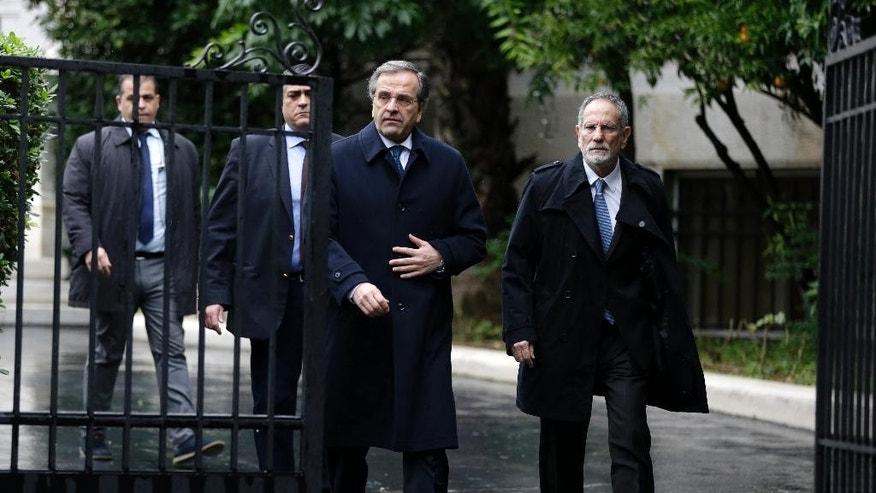 Greece's Prime Minister Antonis Samaras, center, leaves his office for a meeting with Greek President Karolos Papoulias in Athens, Tuesday, Dec. 30, 2014. Parliament failed to elect a new Greek president after three rounds of voting, triggering an early general election on Jan. 25, which could see a pro-bailout coalition lose power. (AP Photo/Thanassis Stavrakis)