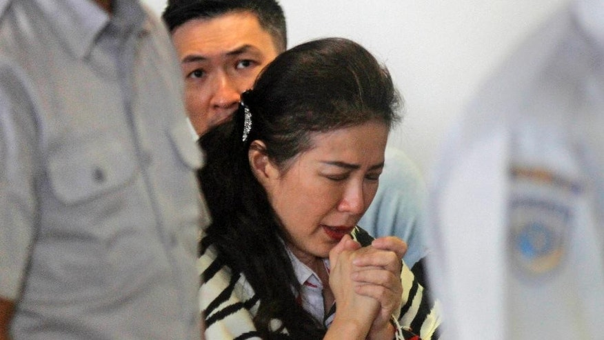 A relative of passengers of the missing AirAsia flight QZ8501 prays at the crisis center at Juanda International Airport in Surabaya, East Java, Indonesia, Tuesday, Dec. 30, 2014. More planes will be in the air and more ships on the sea Tuesday hunting for AirAsia Flight 8501 in a widening search off Indonesia that has dragged into a third day without any solid leads. Flight 8501 vanished Sunday in airspace thick with storm clouds on its way from Surabaya, Indonesia, to Singapore. (AP Photo/Trisnadi Marjan)