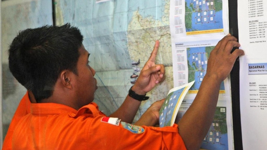 Officers of Indonesian Search And Rescue Agency (BASARNAS) check a map at their command center at Juanda International Airport in Surabaya, East Java, Indonesia, Tuesday, Dec. 30, 2014. More planes will be in the air and more ships on the sea Tuesday hunting for AirAsia Flight 8501 in a widening search off Indonesia that has dragged into a third day without any solid leads. Flight 8501 vanished Sunday in airspace thick with storm clouds on its way from Surabaya, Indonesia, to Singapore. (AP Photo/Trisnadi)