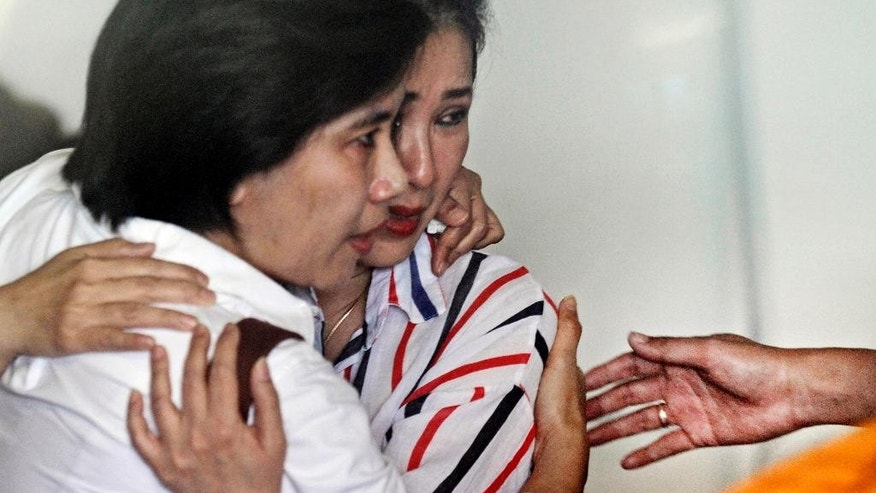 Relatives of passengers of the missing AirAsia flight QZ8501 comfort each other at the crisis center at Juanda International Airport in Surabaya, East Java, Indonesia, Tuesday, Dec. 30, 2014. More planes will be in the air and more ships on the sea Tuesday hunting for AirAsia Flight 8501 in a widening search off Indonesia that has dragged into a third day without any solid leads. Flight 8501 vanished Sunday in airspace thick with storm clouds on its way from Surabaya, Indonesia, to Singapore. (AP Photo/Trisnadi Marjan)