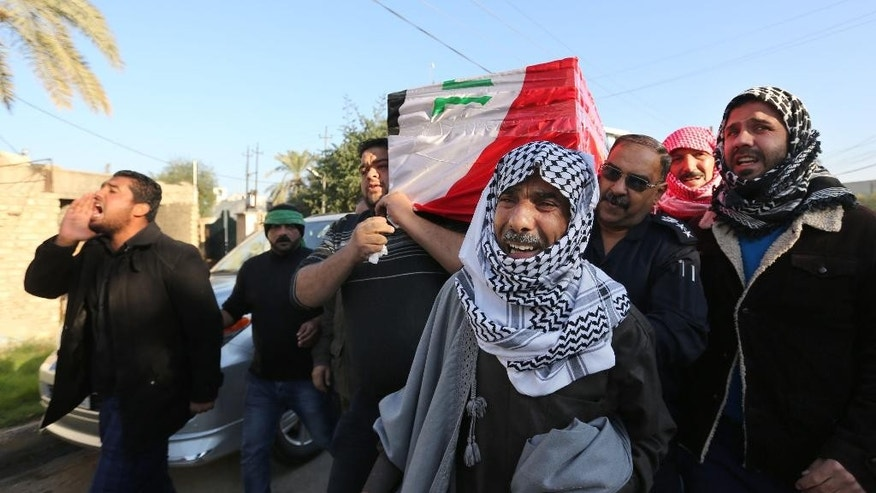 Mourners carry the coffin of Gen. Abbas Hussein, a senior member of the Badr Brigades, a Shiite militia, who was killed during a battle against the Islamic State extremist group in Iraq, during his funeral in Baghdad Iraq, Thursday, Dec. 30, 2014. (AP Photo/Hadi Mizban)