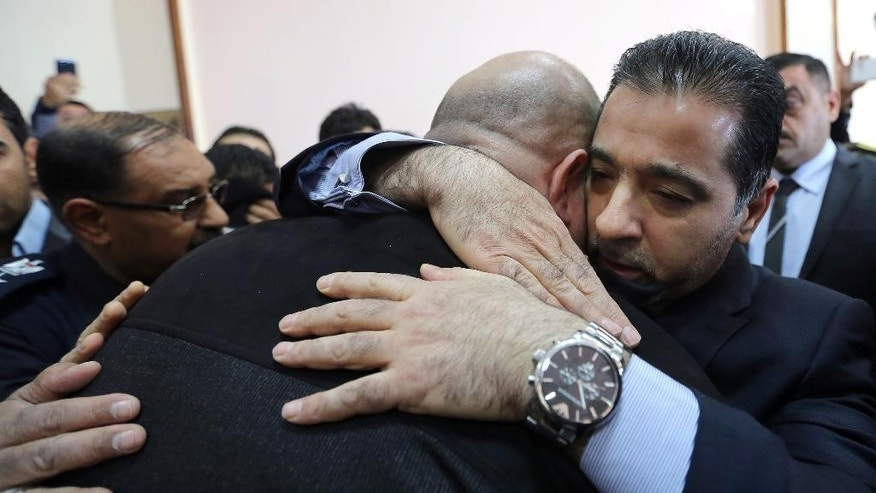 Interior Minister Mohammed al-Gaban, right, embraces a son of Gen. Abbas Hussein, a senior member of the Badr Brigades, a Shiite militia, who was killed during a battle against the Islamic State extremist group in Iraq, during his funeral in Baghdad Iraq, Thursday, Dec. 30, 2014. (AP Photo/Hadi Mizban)