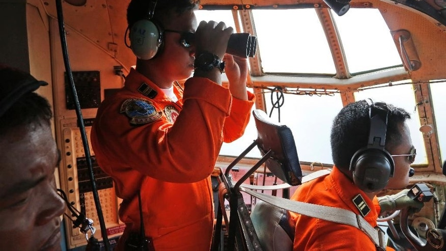 A crew of an Indonesian Air Force C-130 airplane of the 31st Air Squadron uses a binocular to scan the horizon during a search operation for the missing AirAsia flight 8501 jetliner over the waters of Karimata Strait in Indonesia, Monday, Dec. 29, 2014. Search planes and ships from several countries on Monday were scouring Indonesian waters over which an AirAsia jet disappeared, more than a day into the region's latest aviation mystery. AirAsia Flight 8501 vanished Sunday in airspace thick with storm clouds on its way from Surabaya, Indonesia, to Singapore. (AP Photo/Dita Alangkara)