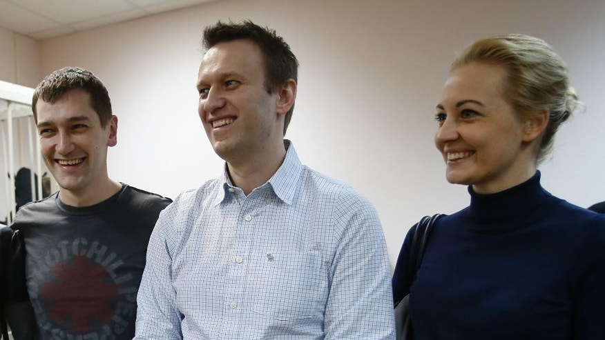 Russian opposition activist and anti-corruption crusader Alexei Navalny, 38, center, his wife Yulia, right, and his brother Oleg Navalny, left, smile at a court in Moscow, Russia, Tuesday, Dec. 30, 2014. The Moscow court on Monday moved up the date of its verdict in a criminal case against President Vladimir Putin's top foe Navalny in an apparent bid to derail a planned protest. (AP Photo/Pavel Golovkin)