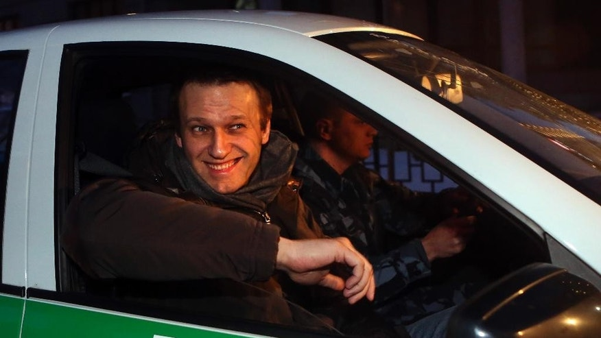 Russian opposition activist and anti-corruption crusader Alexei Navalny, 38, smiles upon arrival at a court in Moscow, Russia, Tuesday, Dec. 30, 2014. The Moscow court on Monday moved up the date of its verdict in a criminal case against President Vladimir Putin's top foe Navalny in an apparent bid to derail a planned protest. (AP Photo/Denis Tyrin)