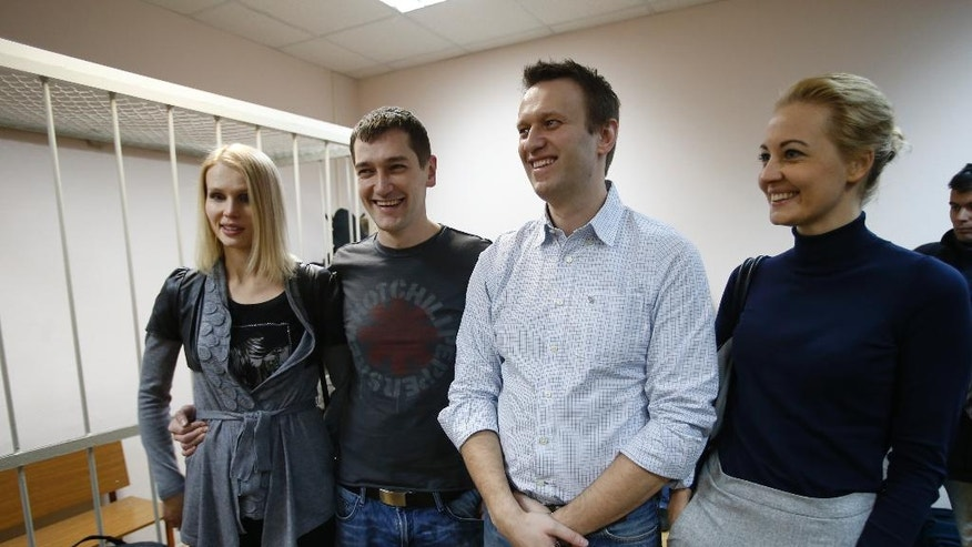 Russian opposition activist and anti-corruption crusader Alexei Navalny, 38, second right, his wife Yulia, right, and his brother Oleg Navalny, second left, with his wife, stand at a court in Moscow, Russia, Tuesday, Dec. 30, 2014. The Moscow court on Monday moved up the date of its verdict in a criminal case against President Vladimir Putin's top foe Navalny in an apparent bid to derail a planned protest. (AP Photo/Pavel Golovkin)