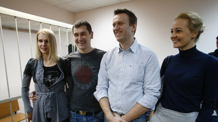 Dec. 30, 2014: Russian opposition activist and anti-corruption crusader Alexei Navalny, 38, second right, his wife Yulia, right, and his brother Oleg Navalny, second left, with his wife, stand at a court in Moscow