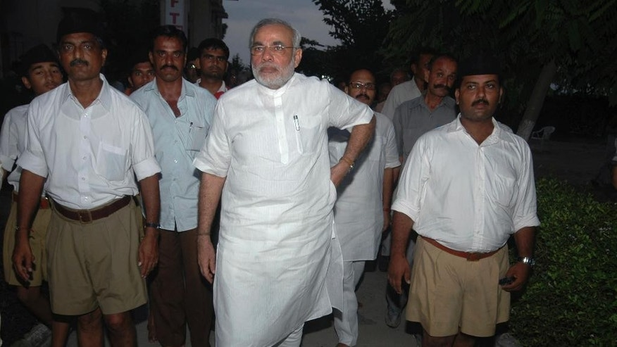 FILE – In this Sunday, Sept. 6, 2009 photo, Gujarat state Chief Minister Narendra Modi, center, leaves after a meeting with Mohan Bhagwat, chief of the Rashtriya Swayamsevak Sangh (RSS), the parent body of the Bharatiya Janata Party (BJP), at a temple in Adalaj, about 20 kilometers (12 miles) north of Ahmadabad, India. While Modi played down religious issues during the 2014 general election campaign, wary of alienating voters with his and his party's reputations for Hindu nationalism, nationalist voters turned out for him in droves. So when Modi was elected, nationalist leaders who had spent years in India's political wilderness began pressing the government to adopt its agenda. Just how much Modi actually supports that sprawling agenda, which includes everything from demands to rewrite school textbooks to, at the most extreme end, the expulsion of non-Hindus from India, remains unclear. (AP Photo/Ajit Solanki, File)