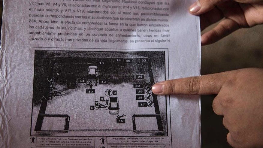 In this Dec. 23, 2014 photo, a woman who spoke on the condition of anonymity in fear retribution by officials and drug traffickers points to a court document showing a map of a grain warehouse in San Pedro Limon, marked with numbers where bodies were found, during an interview at her home in Mexico. In her first interview since being tortured and falsely imprisoned for five months on weapons possession charges, the 20-year-old said a cover-up of a mass killing by the Mexican army went far beyond the seven soldiers facing trial in the case to include more soldiers, and state and federal prosecutors who pushed to make the deaths look like the result of a gun battle rather than what they were-- extra-judicial killings after surrender. (AP Photo/Christian Palma)