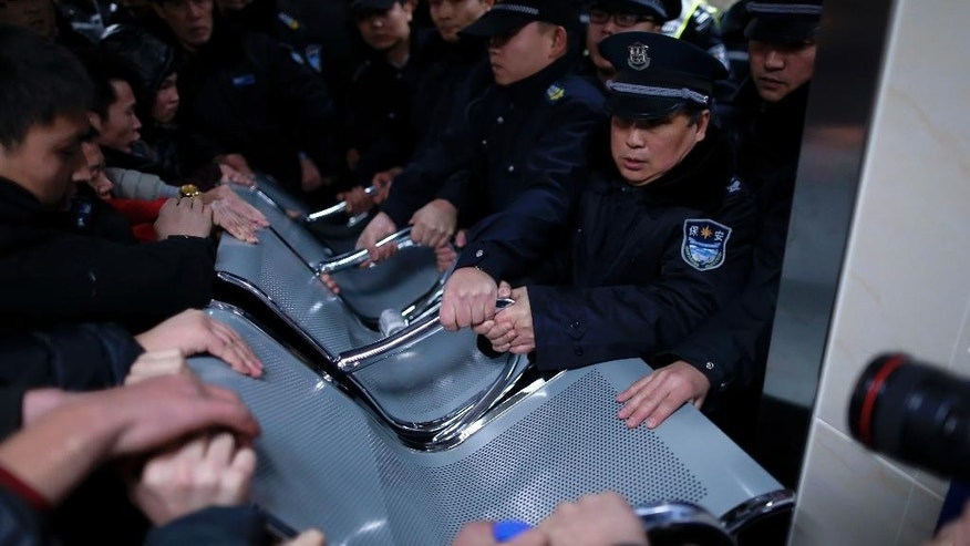Security guards use a bench to hold off relatives of stampede victims trying to enter the emergency area of a hospital in Shanghai, China, Thursday, Jan. 1, 2015. Dozens died in a stampede during New Year's celebrations in downtown Shanghai, city officials said - the worst disaster to hit one of China's showcase cities in recent years. (AP Photo) CHINA OUT