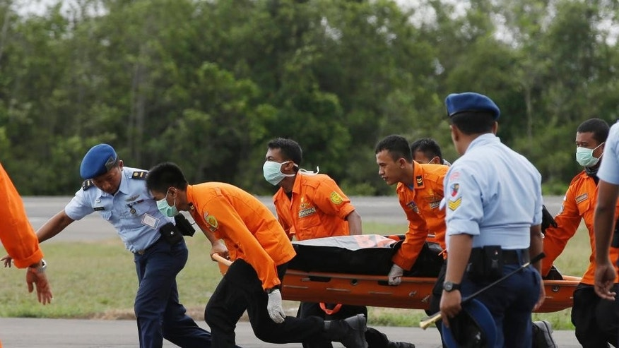 Officers of the National Search And Rescue Agency (BASARNAS) carry a body of one of the victims on board the ill-fated AirAsia Flight 8501, from a helicopter upon arrival at the airport in Pangkalan Bun, Indonesia, Wednesday, Dec. 31, 2014. A massive hunt for the victims of the jet resumed in the Java Sea on Wednesday, but wind, strong currents and high surf hampered recovery efforts as distraught family members anxiously waited to identify their loved ones. (AP Photo/Achmad Ibrahim)