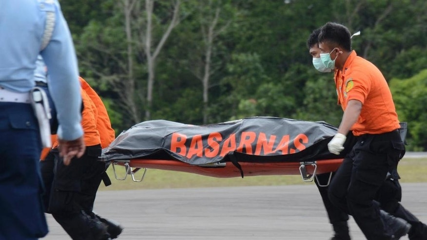 Members of Indonesian National Search And Rescue Agency (BASARNAS) carry the body of a victim of AirAsia Flight 8501 upon arrival at the airport in Pangkalan Bun, Indonesia, Wednesday, Dec. 31, 2014. A massive hunt for the victims of AirAsia Flight 8501 resumed in the Java Sea on Wednesday, focusing on an area of the aqua-colored waters where the first bodies and debris were located a day earlier. But wind, strong currents and high surf hampered recovery efforts as distraught family members anxiously waited to identify their loved ones. (AP Photo/Dewi Nurcahyani)