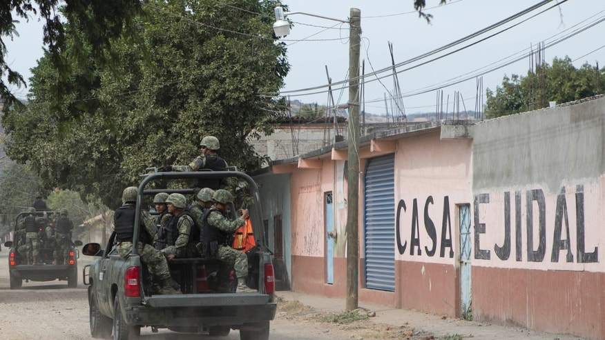 In this Dec. 23, 2014 photo, soldiers patrol the streets of an undisclosed town in Mexico. Two cases have thrown Mexico into a human rights crisis in recent months: a June 30 mass killing by the Mexican army in Mexico state, and 43 college students went missing at the hands of local police in neighboring Guerrero state on Sept. 26. The crimes occurred within three months of each other under the administration of President Enrique Pena Nieto, who had promised more transparency and greater emphasis on human rights, and they have sparked international protests. (AP Photo/Christian Palma)