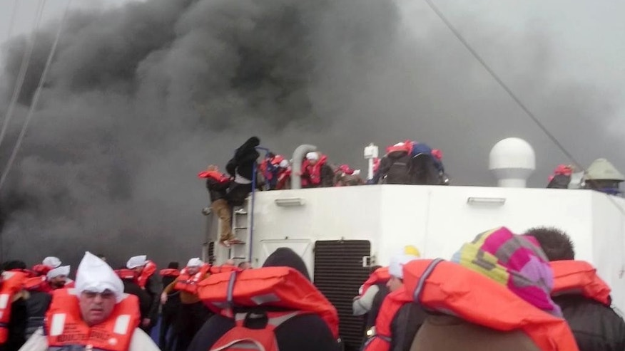In this image taken from a Dec. 28, 2014 video and made available Wednesday, Dec. 31, 2014 passengers of the Italian-flagged ferry Norman Atlantic wait to be rescued after it caught fire in the Adriatic Sea. More than 400 people were rescued from the ferry, most in daring, nighttime helicopter sorties that persisted despite high winds and seas, after a fire broke out before dawn Sunday on a car deck. Both Italian and Greek authorities have announced criminal investigations into the cause of the blaze. Italian authorities warned Tuesday that more bodies will likely be found when the blackened hulk of a Greek ferry is towed to Italy, as part of a criminal investigation into the fire that engulfed the ship at sea, killing at least 11 of the more than 400 people on board. (AP Photo/APTN)